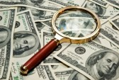 12126110-magnifying-glass-on-a-dollar-background